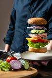 Ingredientes de la hamburguesa que vuelan o del cheeseburger sobre la placa en la mano del hombre en un fondo oscuro Hamburguesa  imagen de archivo libre de regalías