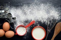 Ingredientes de la hornada en una tabla oscura, de piedra: huevos, harina y leche Imagen de archivo libre de regalías