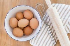 Ingredientes de la hornada, huevos, toalla y herramientas de la cocina en tabl de madera fotos de archivo libres de regalías