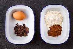 Ingredientes de la hornada para la torta de chocolate en una taza imagen de archivo