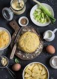 Ingredientes de la hornada - pasta, patatas, queso, puerro, crema Cocinar la empanada con el puerro, la patata y el queso Punto n Fotos de archivo