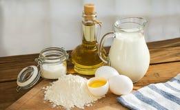 Ingredientes de las crepes Azúcar del aceite de la harina del huevo de la leche Fondo de madera Fotos de archivo libres de regalías