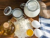Ingredientes de las crepes Azúcar del aceite de la harina del huevo de la leche Fondo de madera Imagenes de archivo