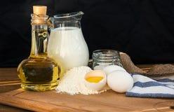 Ingredientes de las crepes Azúcar del aceite de la harina del huevo de la leche Fondo oscuro Fotos de archivo