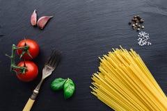 Ingredientes de las pastas en fondo negro de la pizarra Foto de archivo