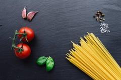 Ingredientes de las pastas en fondo negro de la pizarra Fotografía de archivo libre de regalías