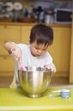 Ingredientes de mezcla de la hornada del niño pequeño en un cuenco Imágenes de archivo libres de regalías