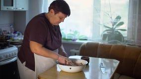 Ingredientes de mezcla de la mujer mayor para el plato tradicional en un cuenco metrajes