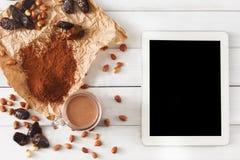 Ingredientes do batido do chocolate na madeira branca com tela da tabuleta Fotos de Stock