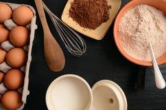Ingredientes do cozimento em uma tabela de pedra: ovos, farinha, açúcar e cacau Imagem de Stock