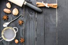 Ingredientes do cozimento no fundo de madeira rústico preto Ferramentas, porcas e especiarias da cozinha na tabela de madeira imagens de stock royalty free