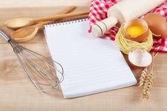 Ingredientes do cozimento para cozinhar e caderno para receitas fotografia de stock