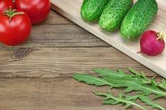 Ingredientes do vegetal de salada na placa de corte de madeira fotografia de stock royalty free