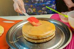 Ingredientes e utensílios do cozimento para cozinhar o bolo de esponja Processo que cozinha o bolo de esponja A mulher põe o crem imagem de stock royalty free