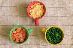 Ingredientes en tazas coloridas Fotos de archivo