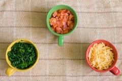 Ingredientes en tazas coloridas Foto de archivo libre de regalías