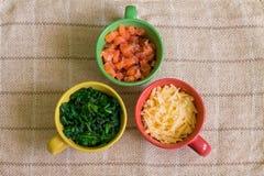 Ingredientes en tazas coloridas Imagen de archivo