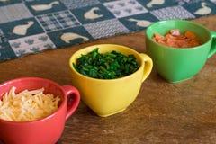 Ingredientes en tazas coloridas en la tabla de madera Imágenes de archivo libres de regalías
