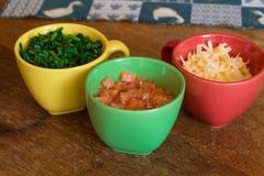 Ingredientes en tazas coloridas en la tabla de madera Fotos de archivo