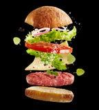 Ingredientes frescos flotantes para una hamburguesa de la carne de vaca Fotografía de archivo