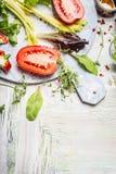 Ingredientes frescos para la ensalada sabrosa en la tabla de cortar blanca redonda y el fondo de madera, visión superior foto de archivo libre de regalías