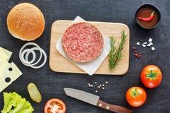 Ingredientes hechos en casa de la hamburguesa en una tabla negra Fotos de archivo libres de regalías