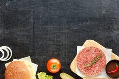 Ingredientes hechos en casa de la hamburguesa en una tabla negra Imagenes de archivo