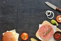 Ingredientes hechos en casa de la hamburguesa en una tabla negra Imágenes de archivo libres de regalías