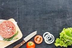 Ingredientes hechos en casa de la hamburguesa en una tabla negra Imagen de archivo