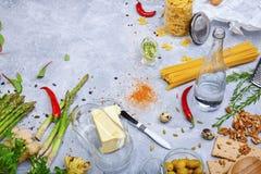 Ingredientes italianos da culinária em um fundo cinzento Aspargo, um recipiente de vidro para a manteiga ao lado da massa e uma g fotografia de stock