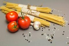 Ingredientes italianos de tomates da massa e dos vegetais, massa, alho, pimenta, queijo, especiarias em um fundo cinzento O conce foto de stock