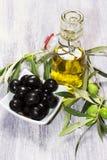 Ingredientes mediterrâneos: azeitonas verdes e pretas e virgen do azeite extra Fotos de Stock