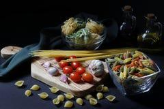 Ingredientes oscuros de las pastas de la comida del claroscuro foto de archivo