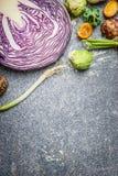 Ingredientes púrpuras de la col y de las verduras para cocinar en el fondo rústico gris, visión superior Concepto del vegetariano Foto de archivo libre de regalías
