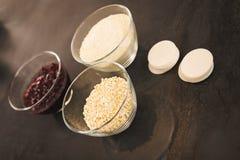 Ingredientes para bolinhos de amêndoa do arando em umas bacias pequenas imagem de stock