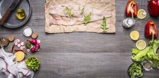 Ingredientes para cocinar bacalao crudo en el papel con la pimienta b de madera rústico de la lechuga de la servilleta de Radisso Fotos de archivo libres de regalías