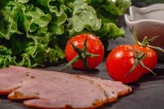Ingredientes para cocinar bruschetta italiano en la tabla oscura Bruschetta italiano con los tomates de cereza, salsa de queso, h foto de archivo