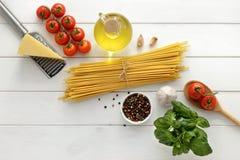 Ingredientes para cocinar bucatini con los tomates, la albahaca, el queso y el ajo en el fondo de madera blanco Foto de archivo libre de regalías