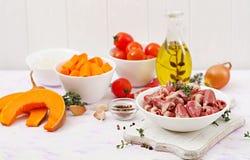 Ingredientes para cocinar corazones del pollo con la calabaza y los tomates en salsa de tomate Imagenes de archivo
