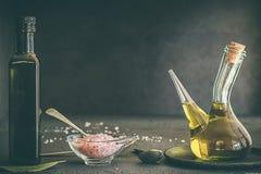 Ingredientes para cocinar el aceite de oliva y la sal Himalayan imagenes de archivo
