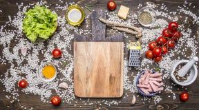 Ingredientes para cocinar el risotto con el jamón, queso, verduras y especias y arroz presentados alrededor de una tabla de corta Imágenes de archivo libres de regalías