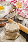 Ingredientes para cocinar la pasta o el pan Huevo quebrado encima de un manojo de harina de centeno blanca Fondo de madera oscuro Fotografía de archivo libre de regalías