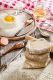 Ingredientes para cocinar la pasta o el pan Huevo quebrado encima de un manojo de harina de centeno blanca Fondo de madera oscuro Fotografía de archivo