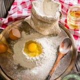 Ingredientes para cocinar la pasta o el pan Huevo quebrado encima de un manojo de harina de centeno blanca Fondo de madera oscuro Fotos de archivo