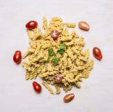 Ingredientes para cocinar las pastas crudas vegetarianas con los tomates de cereza y la opinión superior del fondo rústico de mad Imagen de archivo