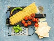 Ingredientes para cocinar las pastas Espaguetis, queso parmesano, tomates de cereza, rallador del metal, aceite de oliva y albaha Foto de archivo libre de regalías