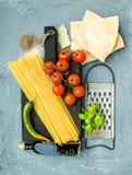 Ingredientes para cocinar las pastas Espaguetis, queso parmesano, tomates de cereza, rallador del metal, aceite de oliva y albaha Fotografía de archivo
