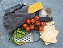 Ingredientes para cocinar las pastas Espaguetis, queso parmesano, tomates de cereza, rallador del metal, aceite de oliva y albaha Imagen de archivo libre de regalías