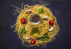 Ingredientes para cocinar las pastas hechas en casa crudas con los tomates de cereza, el perejil, la pimienta y la mantequilla en Fotografía de archivo libre de regalías
