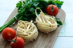 Ingredientes para cocinar las pastas italianas - espagueti, tomates, albahaca y ajo Fotografía de archivo libre de regalías